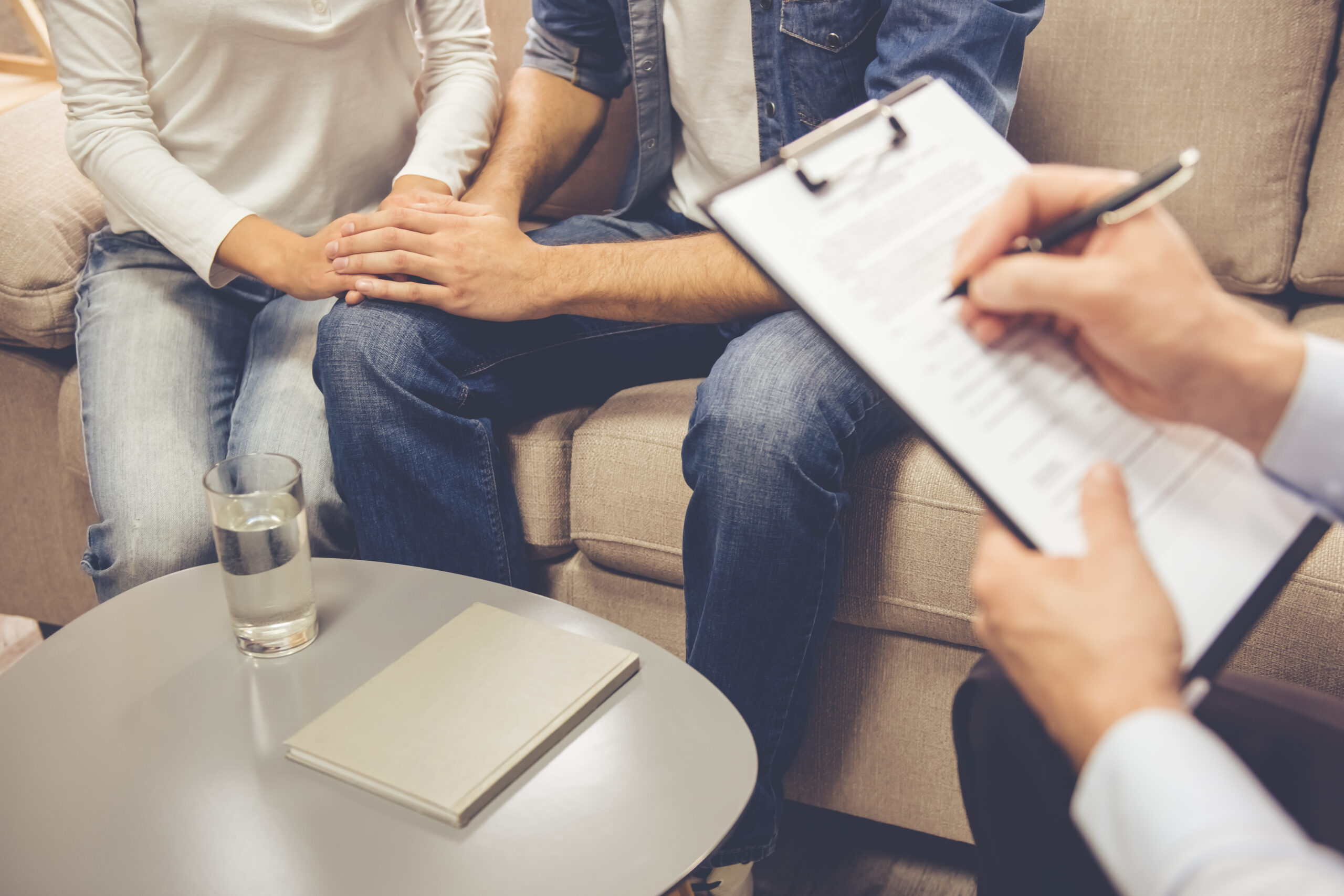 At the psychologist. Cropped image of beautiful young couple sitting on couch and holding hands while doctor is making notes